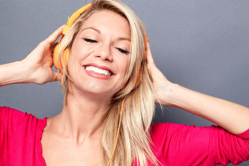 有桃红色毛线衣的轻松的白肤金发的妇女听到音乐的 库存照片