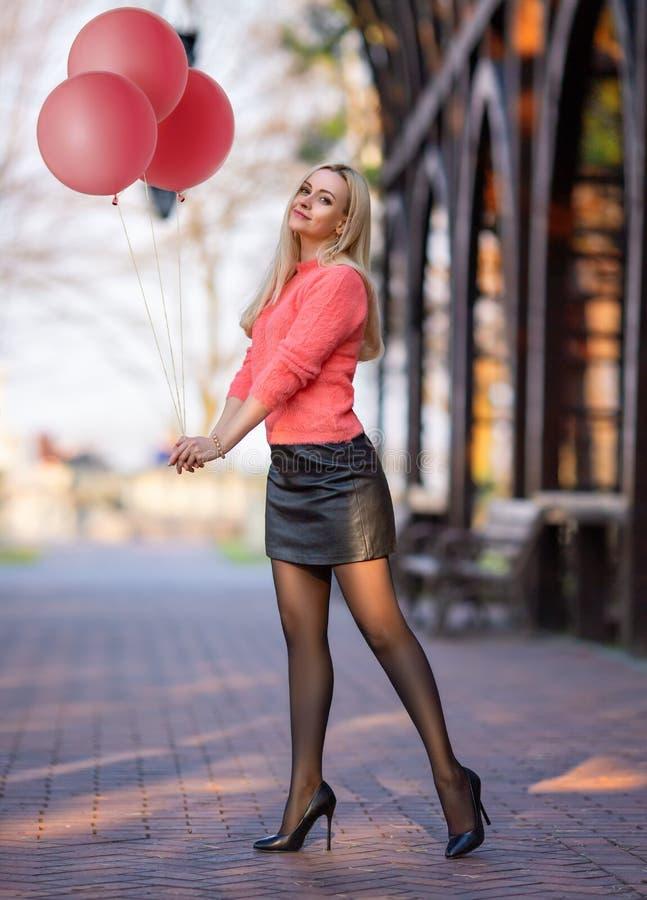 有桃红色气球的女孩在城市广场的裤袜 免版税库存照片