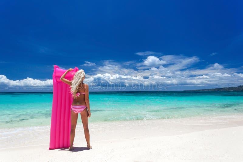有桃红色游泳床垫的妇女在热带海滩,菲律宾 免版税图库摄影
