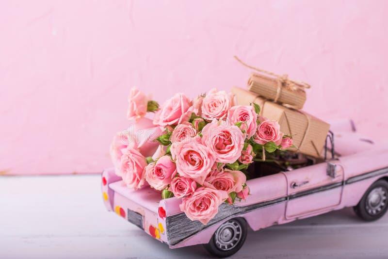 有桃红色玫瑰和被包裹的箱子的减速火箭的汽车玩具有礼物的f 库存照片