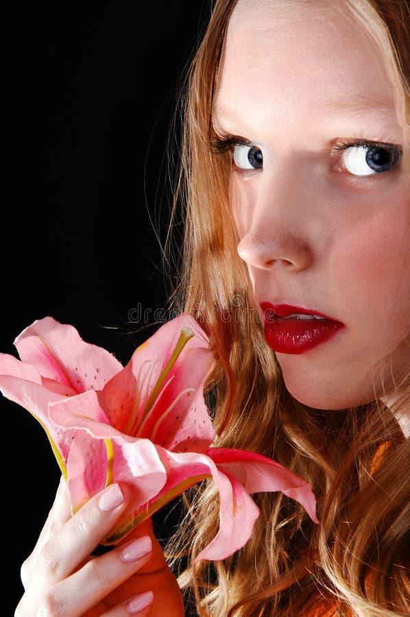 有桃红色百合的女孩。 库存图片