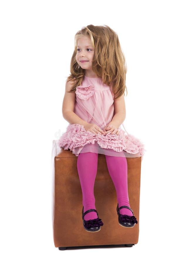 有桃红色礼服的美丽的白肤金发的小女孩坐立方体 图库摄影