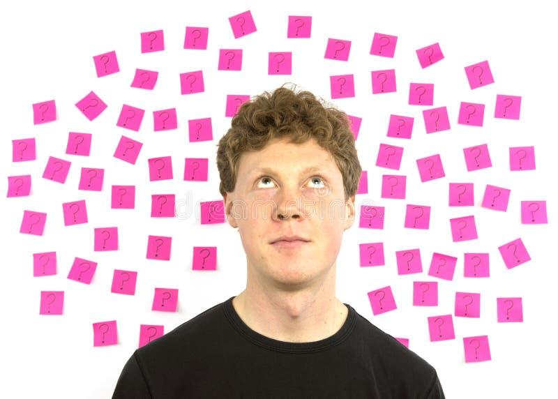 有桃红色粘性附注问号决策的年轻人 免版税图库摄影