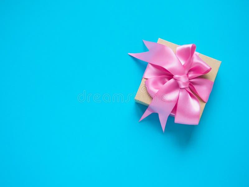 有桃红色缎带的在蓝色背景,文本的拷贝空间一个礼物盒 免版税图库摄影