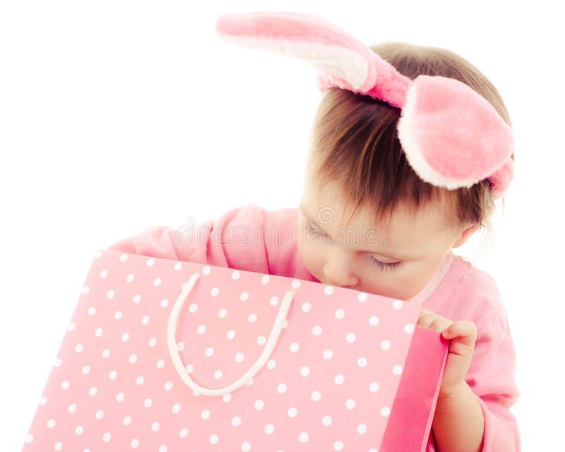 有桃红色耳朵兔宝宝和袋子的小女孩。 库存图片