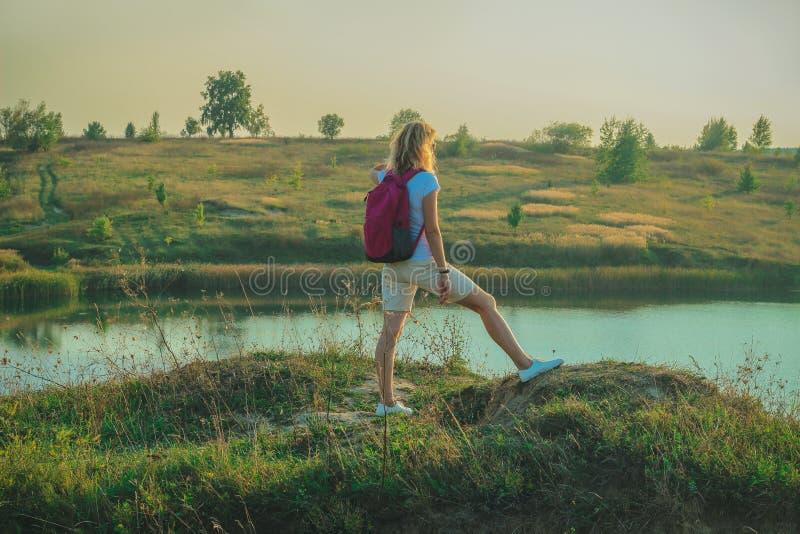 有桃红色背包的年轻女人在蓝色白垩猎物背景关闭站立在日落时间 库存照片