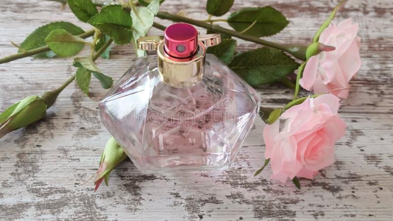 有桃红色芬芳和玫瑰的香水瓶在老木背景 库存图片