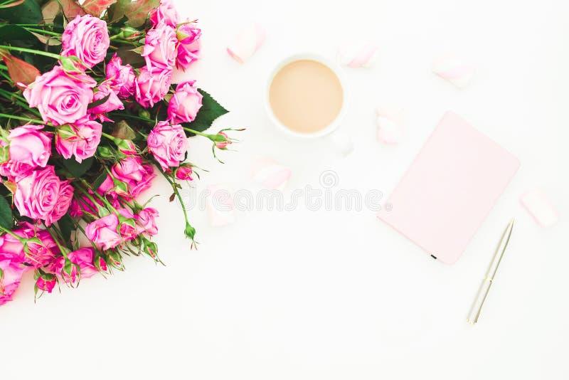 有桃红色花、桃红色日志、咖啡杯和蛋白软糖花束的女性书桌在白色背景 平的位置 女性的顶视图 免版税库存图片