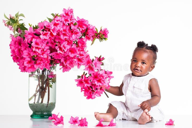 有桃红色花的婴孩 免版税图库摄影