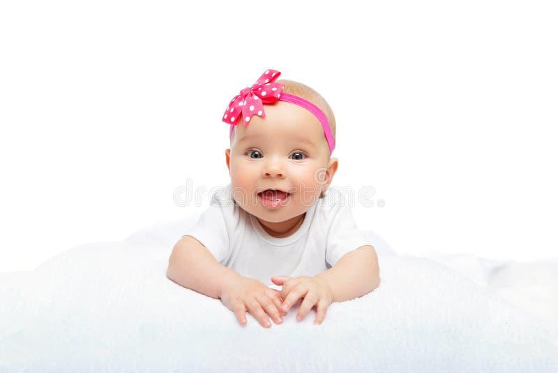 有桃红色花的愉快的美丽的女婴在头 库存图片