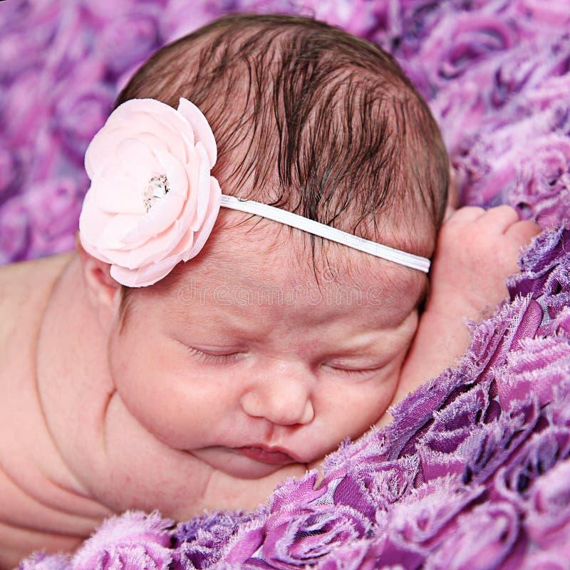 有桃红色花的新出生的女婴 免版税图库摄影