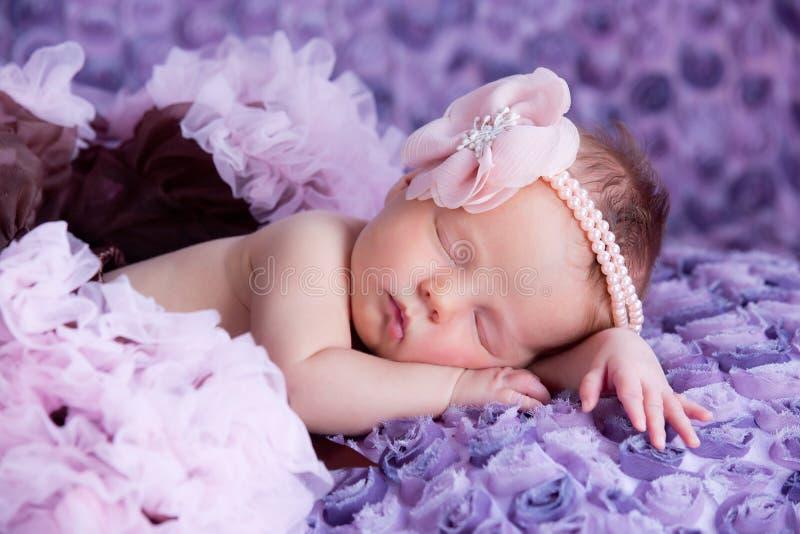 有桃红色花的新出生的女婴 免版税库存照片