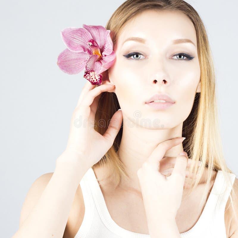有桃红色花的秀丽金发碧眼的女人在头发 清楚和新鲜的皮肤 秀丽表面 免版税库存图片
