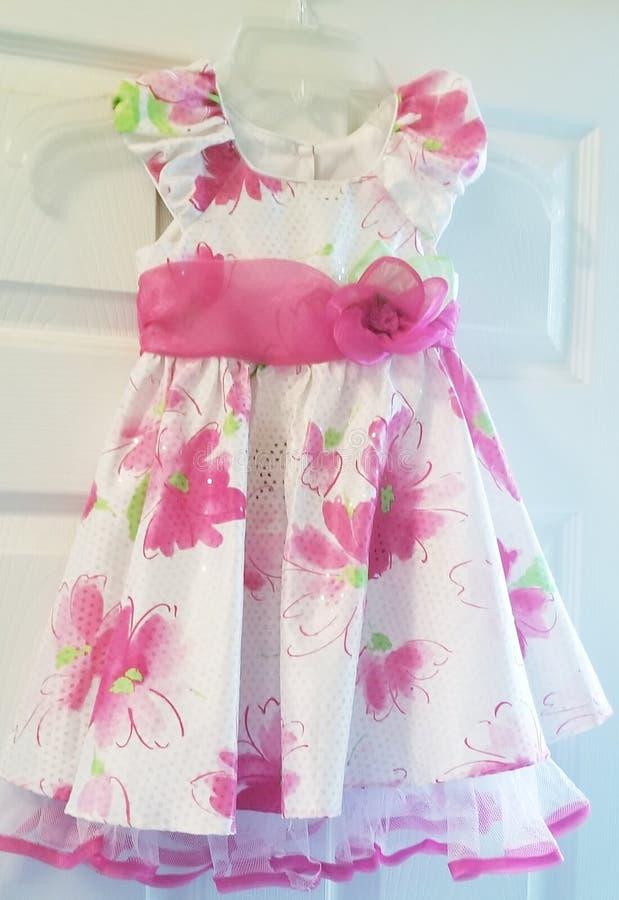 有桃红色花花梢晚礼服的白色礼服孩子的 库存照片