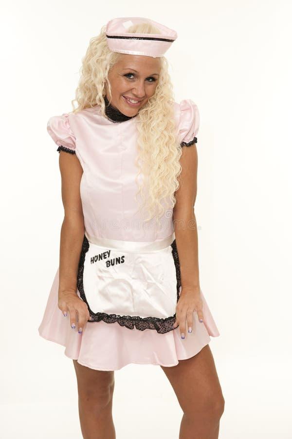 有桃红色衣服的减速火箭的女服务员 免版税库存图片