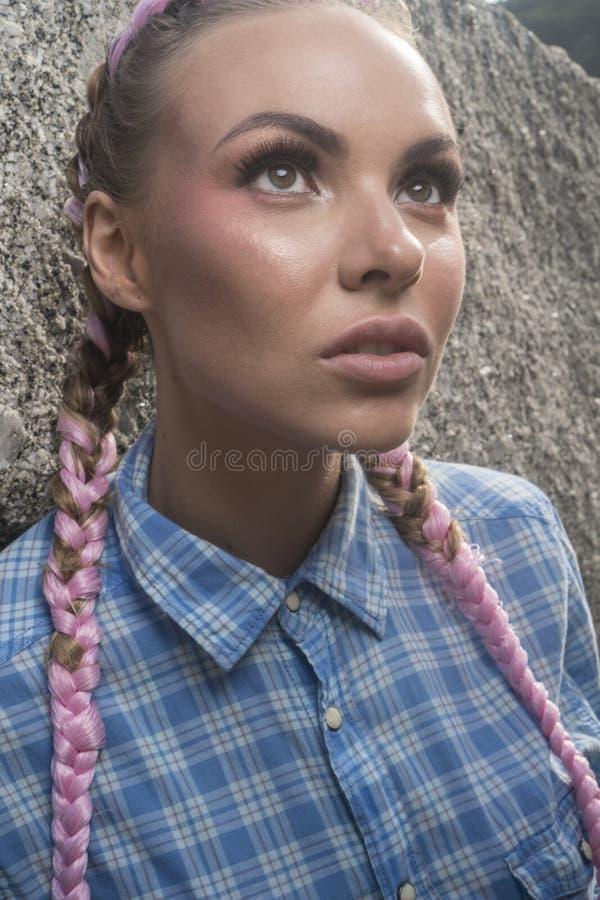 有桃红色褶的年轻俏丽的女孩在岩石之间 免版税库存图片