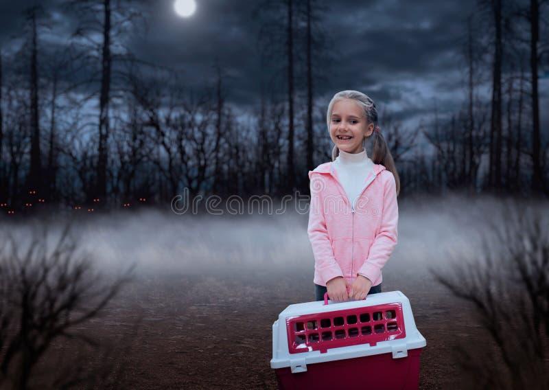 有桃红色载体的愉快的小女孩在森林里 库存图片