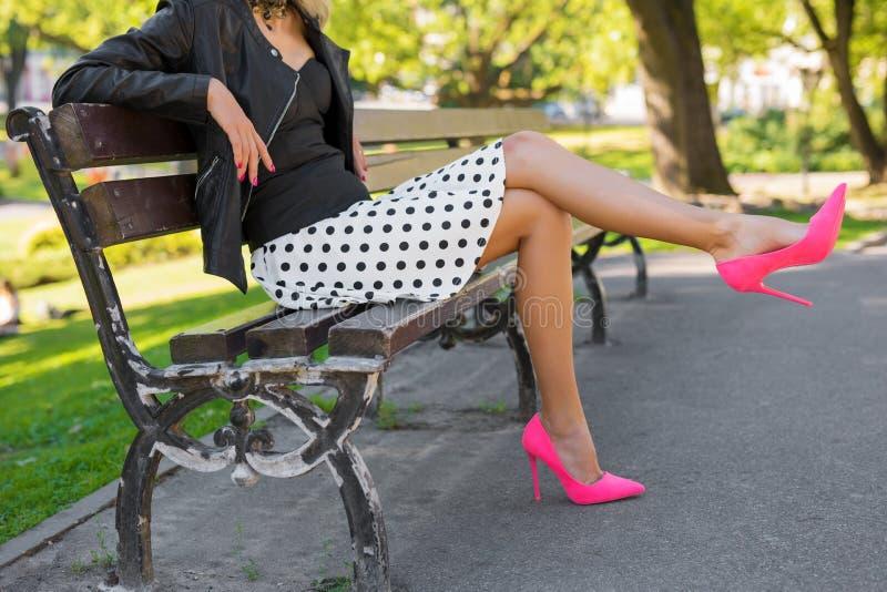 有桃红色鞋子的时髦的妇女坐长凳在公园 免版税库存图片