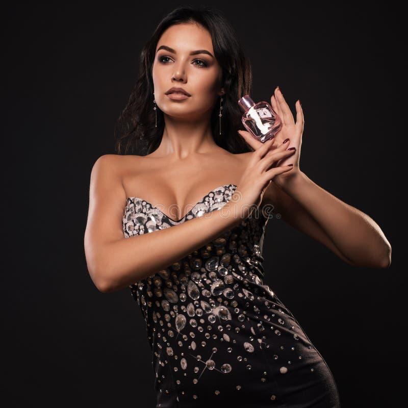 有桃红色香水瓶的美丽的妇女在灰色背景 免版税图库摄影