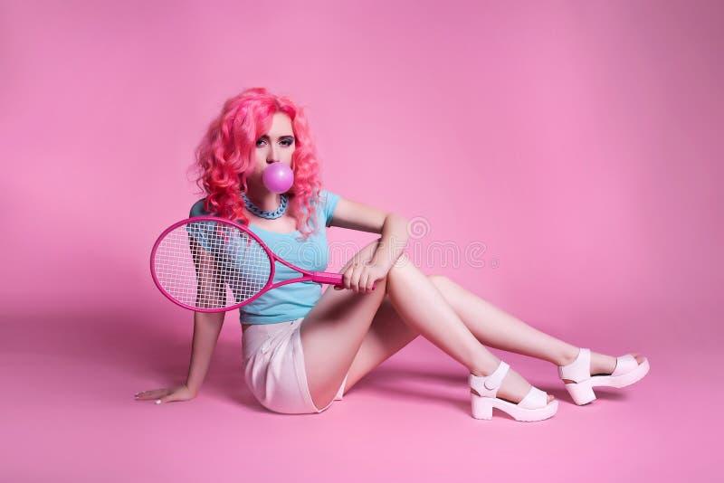有桃红色头发的女孩打在一个桃红色背景和口香糖的网球 免版税图库摄影
