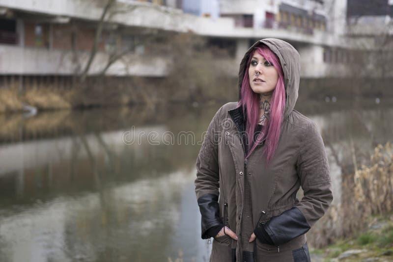 有桃红色头发的妇女在荒凉的周围 库存图片