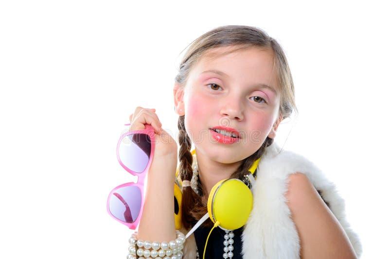 有桃红色玻璃和黄色耳机的一个相当小女孩 免版税库存图片