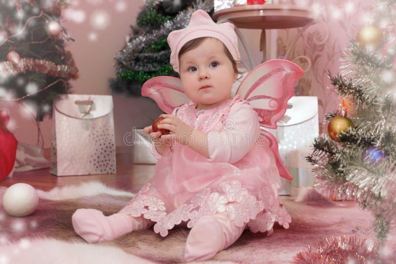 有桃红色蝴蝶的女婴飞过坐在圣诞树下 免版税库存照片