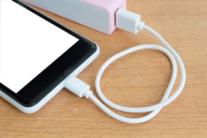 有桃红色powerbank的智能手机在木书桌上 库存照片