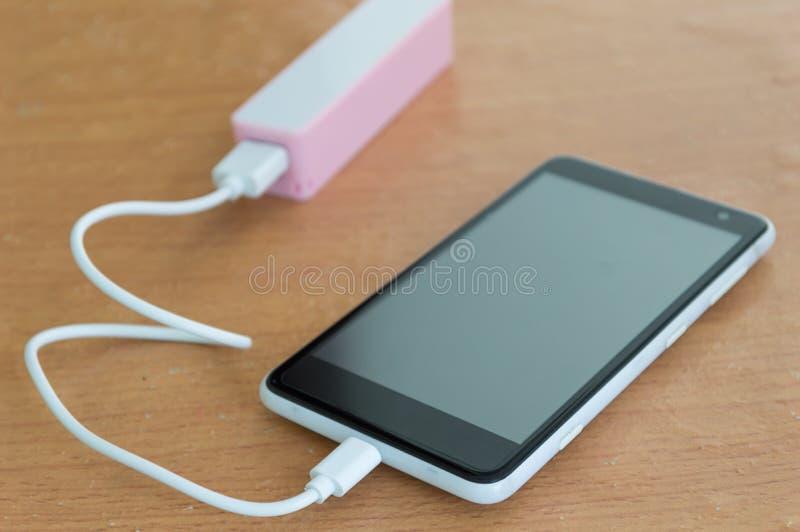 有桃红色powerbank的黑智能手机在木书桌上 图库摄影