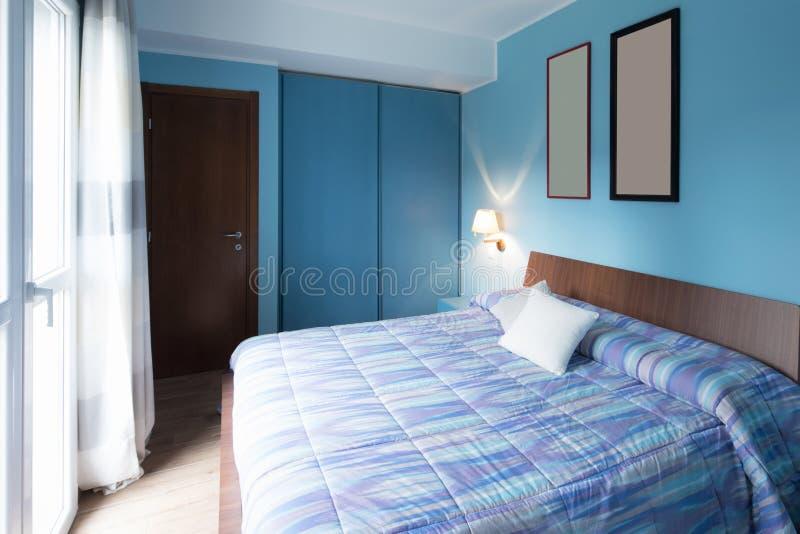 有框架的蓝色卧室在墙壁上 免版税图库摄影
