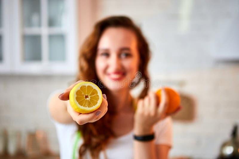 有桔子和柠檬柑橘的年轻愉快的妇女在现代厨房里 健康食品和节食的概念 疏松重量 库存图片