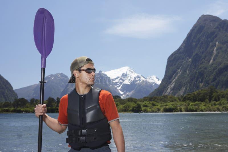 有桨的人在Mountain湖前面 免版税库存图片