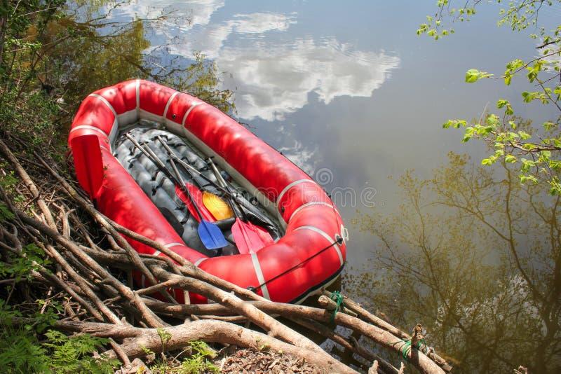 有桨的红色可膨胀的小船为漂流漂流沿河 免版税库存照片