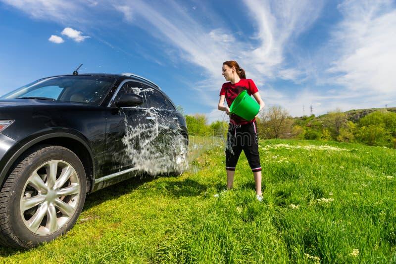 有桶的妇女洗涤的汽车在领域的水 免版税库存照片
