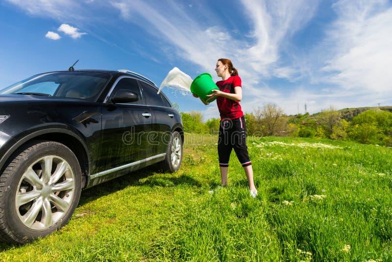 有桶的妇女洗涤的汽车在领域的水 免版税库存图片