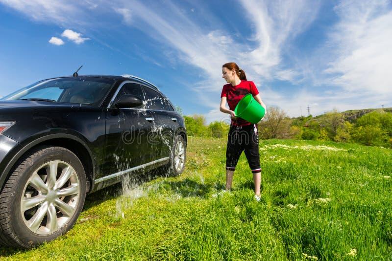 有桶的妇女洗涤的汽车在领域的水 库存照片