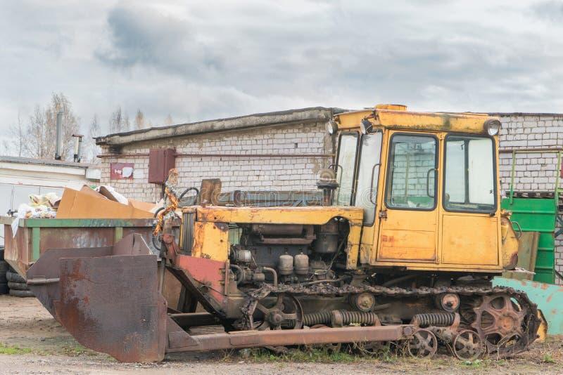 有桶的老生锈的黄色被放弃的拖拉机 免版税库存图片