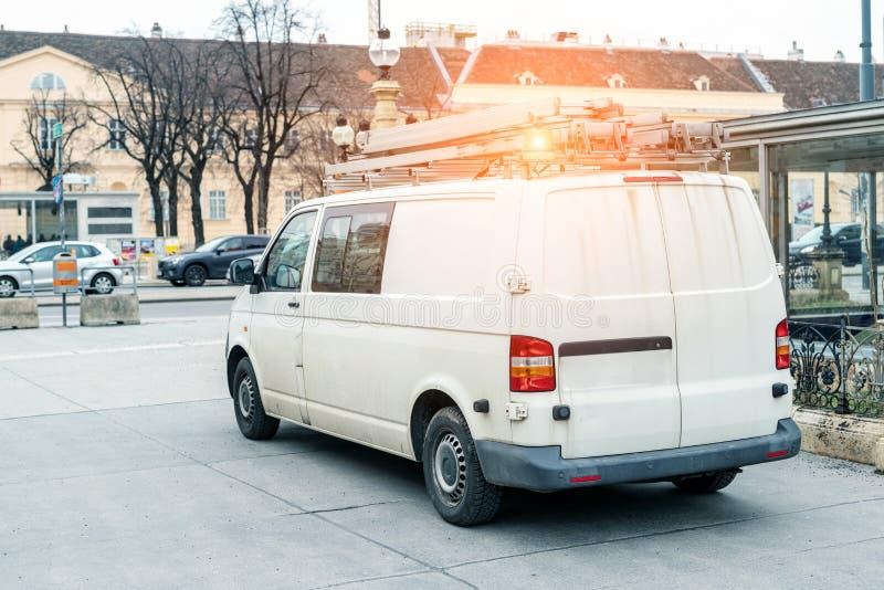 有梯子的白色修理和服务搬运车和在屋顶的橙色光酒吧在城市街道 协助或设施队车 库存照片