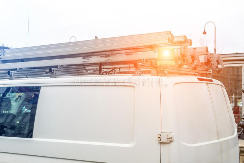 有梯子的白色修理和服务搬运车和在屋顶的橙色光酒吧在城市街道 协助或设施队车 免版税图库摄影
