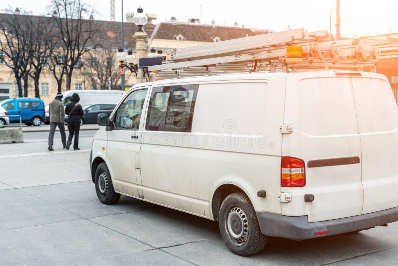 有梯子的白色修理和服务搬运车和在屋顶的橙色光酒吧在城市街道 协助或设施队车 免版税库存照片