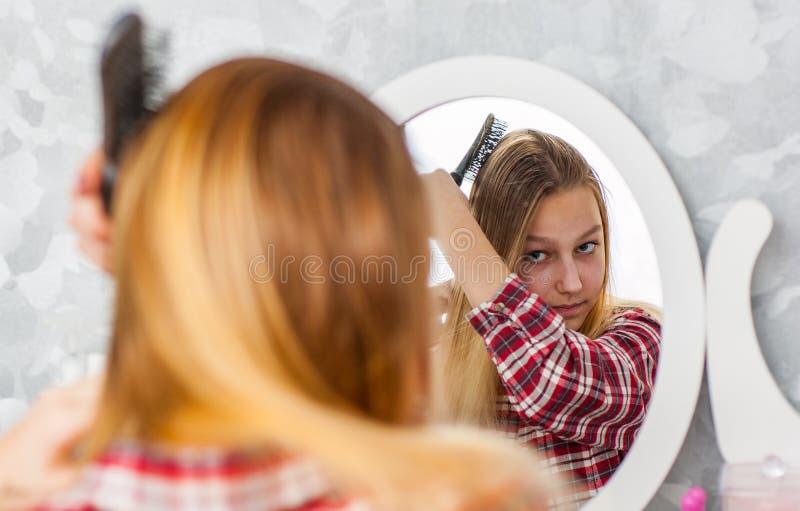 有梳她的在她的镜子前面的长发的年轻少年女孩头发 免版税库存图片