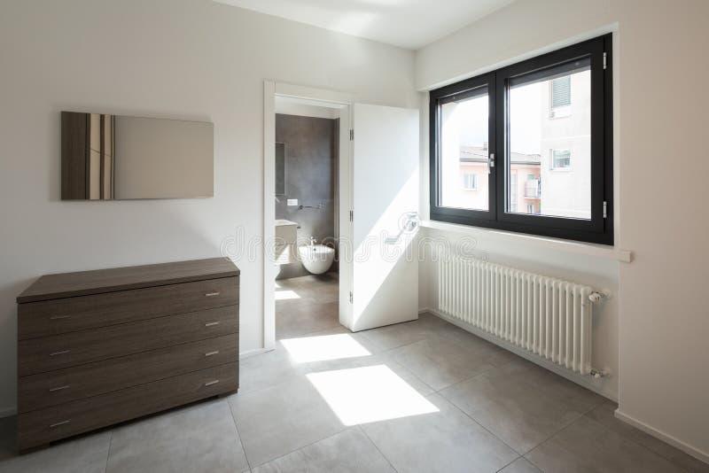 有梳妆台的卧室和私人浴室在屋子里 免版税库存照片