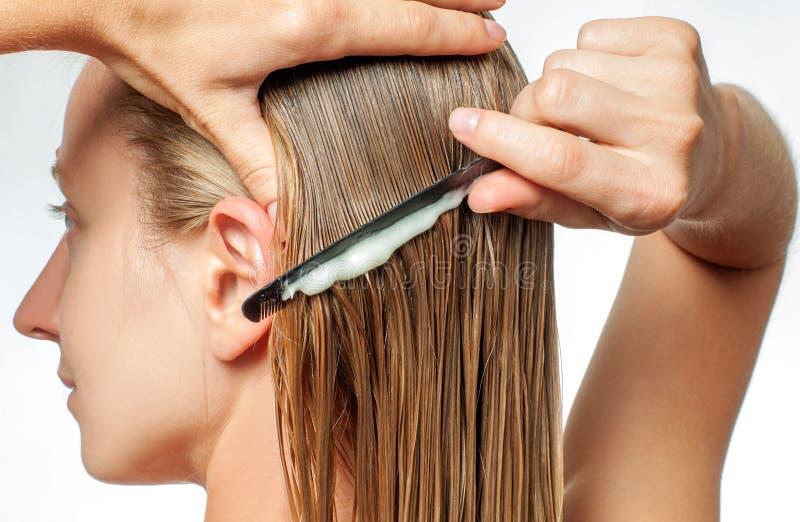 有梳子的妇女应用在她的湿金发的护发素 图库摄影