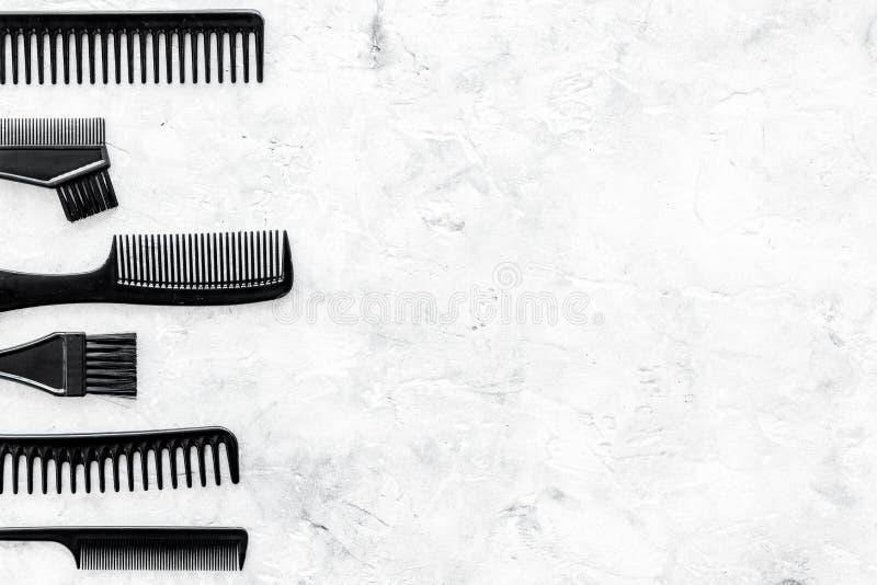 有梳子的,为称呼在灰色石书桌背景顶视图嘲笑的头发的工具美发师运转的书桌  图库摄影