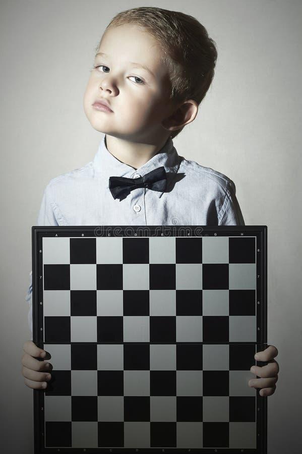 有棋枰的严肃的小男孩 化妆舞会Soldier.Unusual制服 弓领带 小天才孩子 库存图片