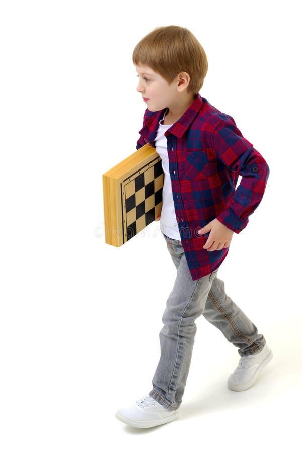 有棋枰的小男孩 库存图片