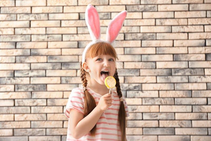 有棒棒糖和兔宝宝耳朵的逗人喜爱的女孩在砖墙附近 免版税库存照片
