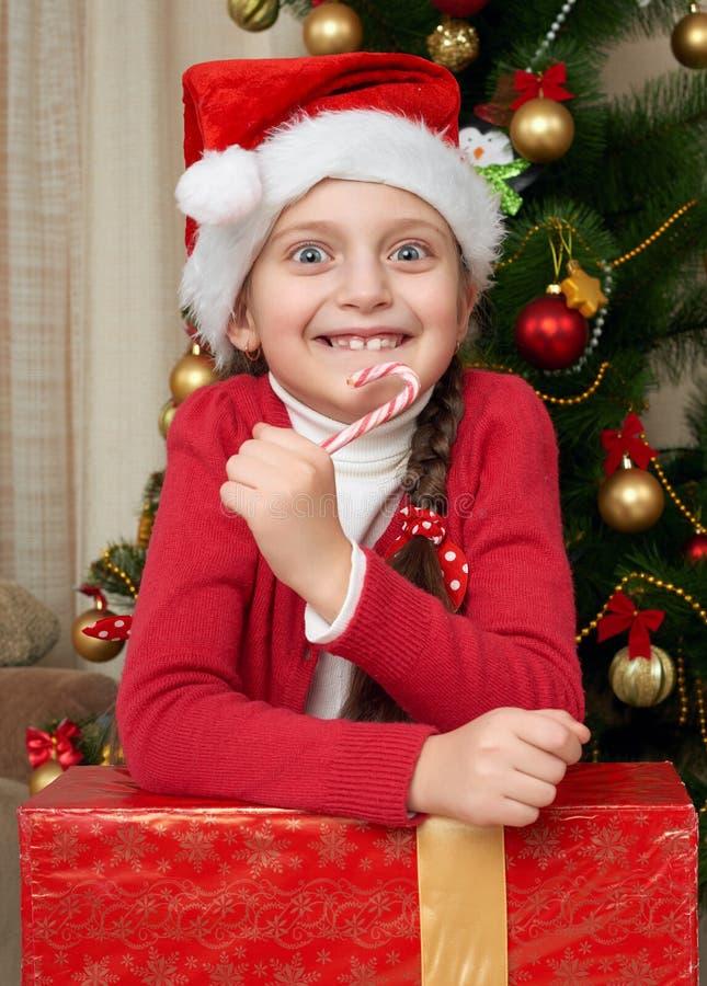 有棒棒糖画象的女孩在圣诞树、装饰和礼物,寒假概念附近 免版税库存照片