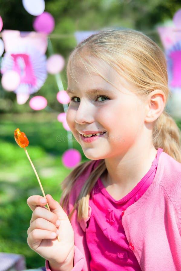 有棒棒糖的愉快的小女孩户外 库存图片