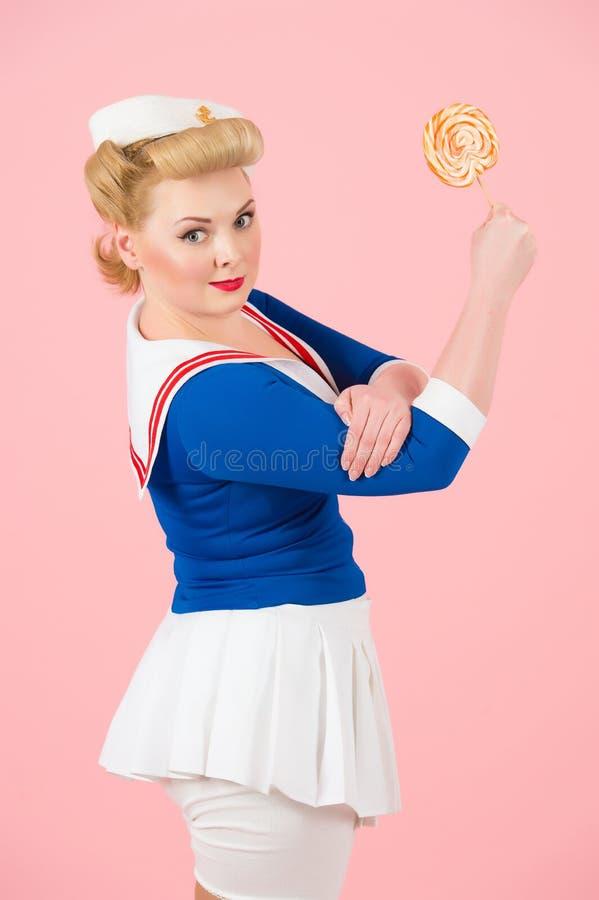 有棒棒糖的芳香树脂水手白肤金发的女孩在手中  我们可以做它称呼了女孩 图库摄影